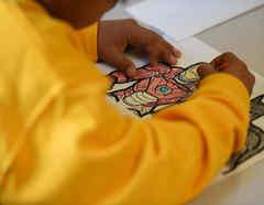 Un niño migrante detenido colorea un libro en el South Texas Family Residential Center.
