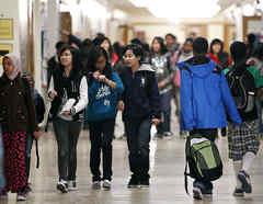 Varios estudiantes caminan por los pasillos de uns institución escolar.