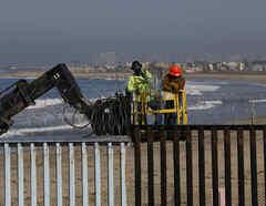 Dos trabajadores instalan alambre de púas en la columna de acero que divide Estados Unidos de México en las costas del Océano Pacífico.