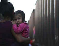 Una madre migrante y su hijita esperan un tren para atravesar México.