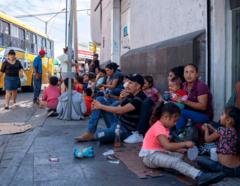 Inmigrantes esperan cerca del puente Paso del Norte en Ciudad Juárez, Chihuahua