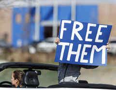 Un manifestante sostiene un cartel de protesta para exigir la liberación de inmigrantes detenidos por ICE por la pandemia de coronavirus.