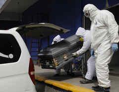 Trabajadores cargan un automóvil con el ataúd de una víctima de coronavirus en Ciudad de México.