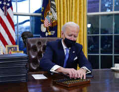 El presidente Joe Biden alcanza un bolígrafo para firmar su primera orden ejecutiva en la oficina Oval.