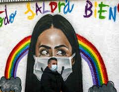 Un hombre usando una mascarilla camina frente a un grafiti.