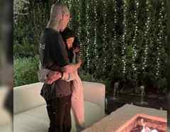 Kourtney Kardashian y Travis Barker abrazados alrededor de una fogata