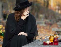 Mujer al lado de una tumba