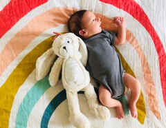 Bebé recostado en manta de arcoíris