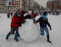 Personas jugando con bolas de nieve en Madrid, España