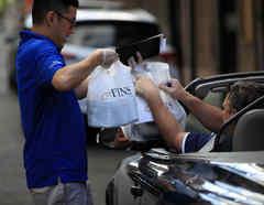 Un mesero en Nueva Orleans entrega comida a un cliente directamente en su auto, en medio de la pandemia de coronavirus en Nuevas Orleans, Louisiana. Allí se han reportado por lo menos 57 muertes como consecuencia del COVID-19.