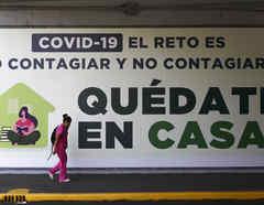 Una mujer camina frente a un letrero que pide quedarse en casa; muchas mexicanas no pueden hacerlo por necesidades económicas o por problemas de violencia en el hogar.