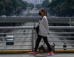 Una mujer con mascarilla camina con su perro por la avenida Libertador en Caracas el pasado 14 de mayo, en medio de la pandemia de coronavirus.