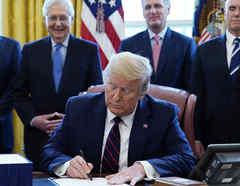 El presidente Donald Trump cuando firmó el primer paquete de ayuda económica ante la pandemia.