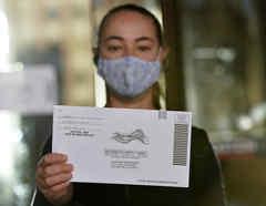 Una mujer sostiene una papeleta prepagada, enviada por correo, antes de depositarla en el buzón, en Boston, Massachusetts.