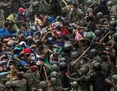 Soldados y policías guatemaltecos golpean a un grupo de migrantes hondureños que caminan por una carretera en Chiquimula este domingo.