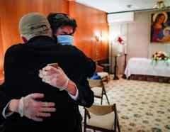 Leonardo Cabaña es consolado por su amigo Raphael Benavides al lado del ataud de su padre, Héctor Miguel Cabaña, quien murió por COVID-19 en Brooklyn, Nueva York, en mayo del 2020.