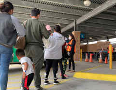 Migrantes liberados por la Patrulla Fronteriza se disponen a abordar un autobús en Brownsville