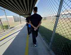 Los detenidos caminan con las manos cruzadas detrás de la espalda dentro del Centro Correccional de Winn en Winnfield, Louisiana, el 26 de septiembre de 2019.