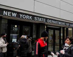 Varias personas esperan en la puerta de una oficina de desempleo en Nueva York.