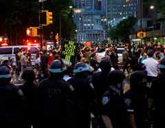 Los oficiales de policía observan cómo los manifestantes marchan a lo largo de una calle en protesta por la muerte en la custodia policial de George Floyd en Minneapolis, en la ciudad de Nueva York, Nueva York, EE.UU.