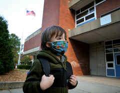 Un niño llega para el primer día de clases en la Escuela Comunitaria Lincoln-Hancock en Quincy, Massachusetts.