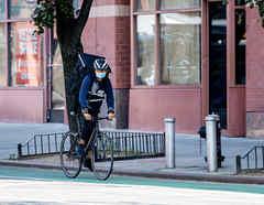Un repartidor de bicicletas usa una máscara en el centro de Manhattan durante la cuarta fase de la reapertura del coronavirus en Nueva York, Nueva York.