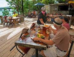 Alexeen Simms, un camarero en el restaurante Hungry Tarpon en Islamorada, Florida, ofrece un almuerzo a una pareja.