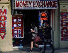 La gente pasa junto a un tablero que muestra los tipos de cambio del peso mexicano frente al dólar estadounidense y el euro frente a una casa de cambio en la Ciudad de México