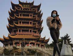 Una mujer visita con una mascarilla un sitio turístico popular en Wuhan en la provincia de Hubei, en el centro de China, donde la vida ya ha vuelto a la normalidad.