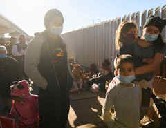 Solicitantes de asilo de países como Honduras esperan fuera del puerto fronterizo de El Chaparral para cruzar a los Estados Unidos en Tijuana, estado de Baja California, México, el 19 de febrero de 2021.
