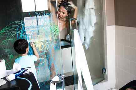 Mujer bañándose mientras su hijo pinta la puerta