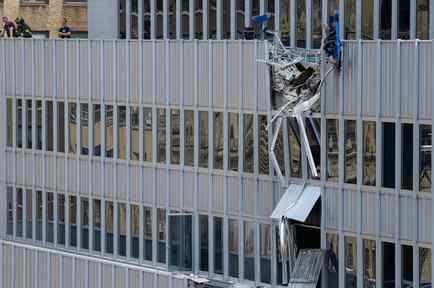 Bomberos observan daños después que una carga que levantaba una grúa cayera del piso 28 en New York