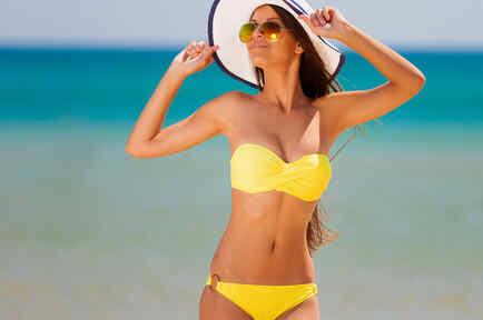 Mujer en la playa con un bikini amarillo