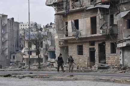 Soldados caminando entre los escombros en Alepo