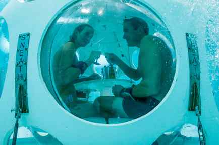 """Belgians Florence Lutje Spelberg and Nicolas Mouchart drink champagne while sitting inside """"The Pearl"""", a spheric dining room placed 5 metres underwater in the NEMO33 diving center in Brussels"""