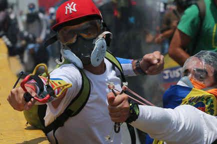 Manifestantes antigubernamentales tiran con hondas durante enfrentamientos con las fuerzas de seguridad que les impiden marchar al centro de Caracas, Venezuela, el miércoles 26 de abril de 2017.