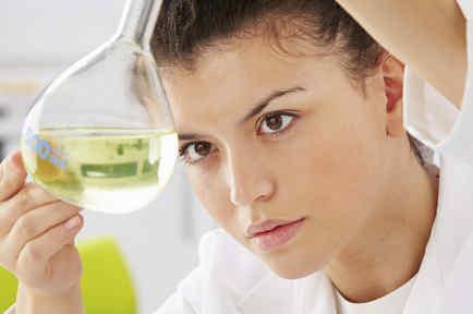Científica examinando un líquido en un frasco