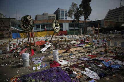 Coronas de flores, ropa, materiales de costura y un maniquí se organizan en un monumento que incluye consignas de protesta en el sitio de una fábrica textil que se derrumbó en el terremoto de 7,1 grados de la semana pasada en la Ciudad de México