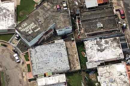Número de teléfono pintado en el techo de un edificio en Arecibo, Puerto Rico
