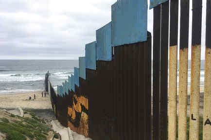 Varias personas se encuentran en el lado mexicano de la frontera con Estados Unidos en Tijuana, México, en una foto de archivo.