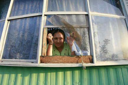 Una inmigrante sonríe desde la ventana de su casa, un tráiler ubicado en el Desert Mobile Home Park, en Thermal, California.