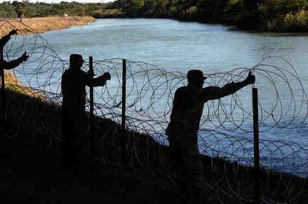 Miembros del ejército de Estados Unidos instalan una cerca de alambre de púas en las orillas del Río Grande, cerca del puente Juárez-Lincoln en la frontera entre México y Estados Unidos el viernes 16 de noviembre de 2018 en Laredo, Texas.