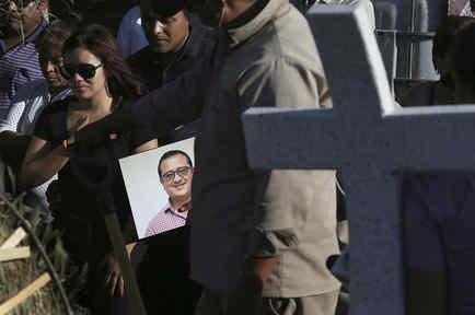 Un hombre sostiene el retrato del periodista Héctor González Antonio mientras que su hija, a la izquierda, llora durante su funeral en la Ciudad de México. González, que trabajaba con el periódico nacional Excelsior, fue encontrado muerto en Ciudad Victor
