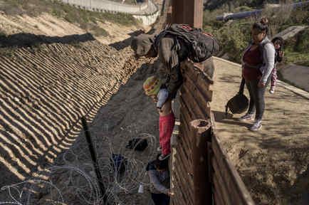 Un hombre pasa a un bebé mexicano a su madre tras saltar la valla fronteriza cerca de Tijuana.