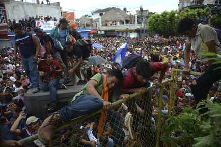 Miles de migrantes corren hacia México, luego de romper las rejas fronterizas, por el puente de Tecun Uman en la frontera con Guatemala, en esta fotografía de archivo del 19 de octubre de 2019.