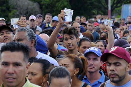 Un joven muestra sus identificaciones de Venezuela y Colombia mientras espera para cruzar el puente SImón Bolívar.