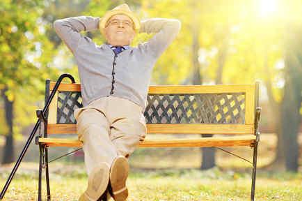 Adulto mayor relajado en un banco de plaza