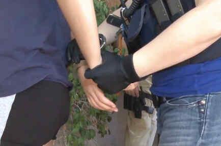 Foto de archivo: Inmigrante arrestado y en proceso de ser esposado