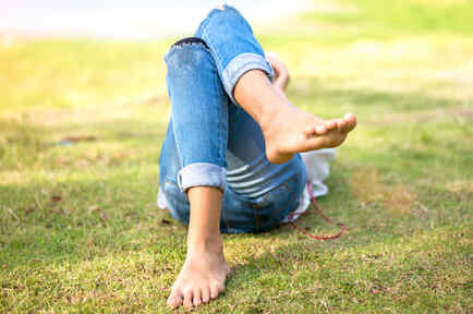 Mujer recostada sobre la hierba, descalza