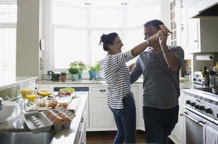 Pareja feliz bailando en la cocina